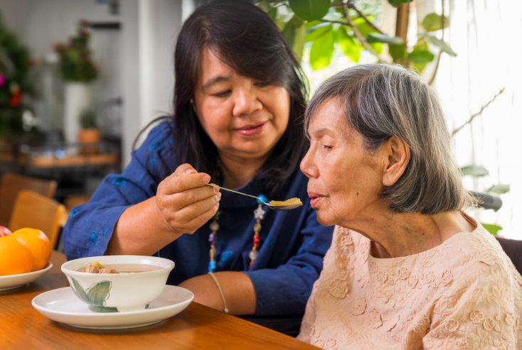 caregiver feeding the elderly